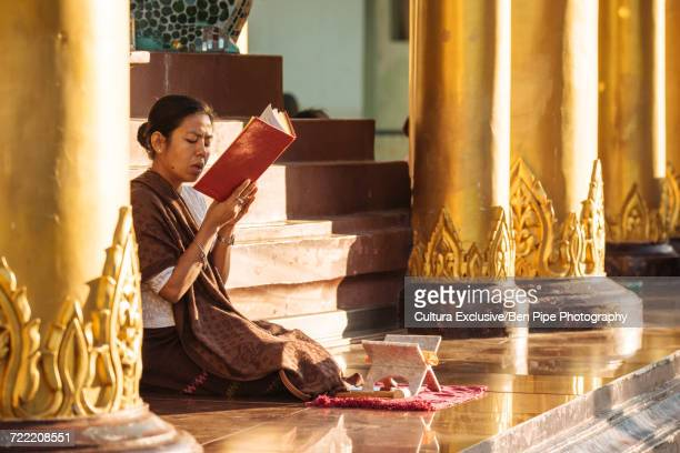 buddhist nun in temple reading, shwedagon pagoda, yangon, myanmar - nun stock-fotos und bilder