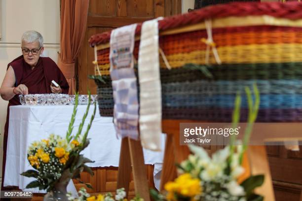 A buddhist nun lights candles beside the willow eco coffin of Jon Underwood at the Jamyang Buddhist Centre on July 6 2017 in London England The...