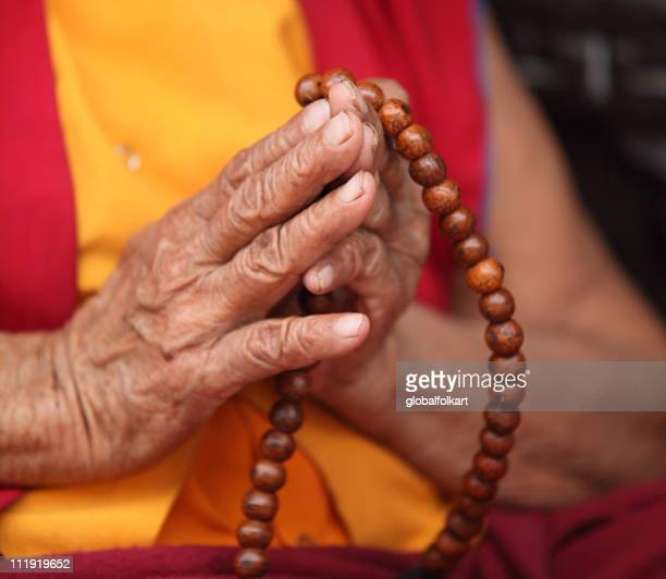 buddhist nun praying with mala prayer beads - tibetan culture stock pictures, royalty-free photos & images
