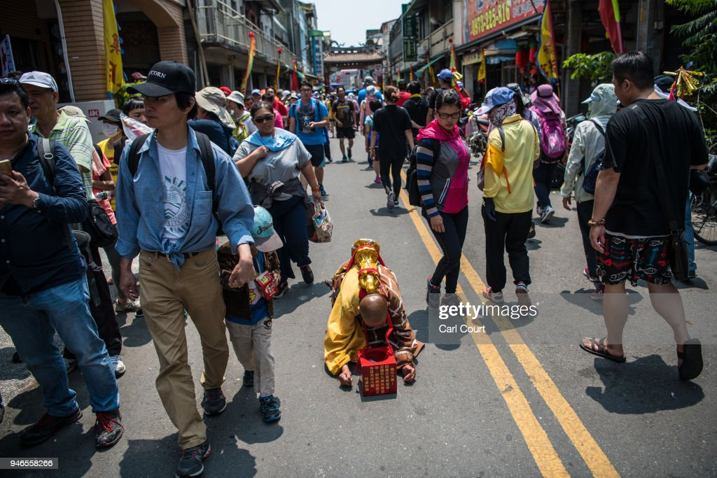 A Buddhist nun prostrates herself as she moves along a street near Houtian Temple on day three of the nine day Mazu pilgrimage on April 15, 2018 in Xizhou, Taiwan. The annual Mazu Pilgrimage begins at Jenn Lann Temple in Taichung and sees around 200,000 pilgrims walk up to 12 hours each day for nine days carrying a statue of Chinese sea goddess Mazu in a sedan chair. The journey covers around 350 kilometres, much of it through mountainous and rugged terrain and visits more than 100 temples before returning to Taichung. The centuries-old pilgrimage is now recognised by UNESCO as living heritage and with an estimated 5 million participants spread over the nine days, it is considered to be one of the greatest religious festivals in the world.