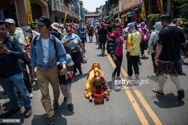 Buddhist nun prostrates herself as she moves along a street near Houtian Temple on day three of the nine day Mazu pilgrimage on April 15 2018 in...