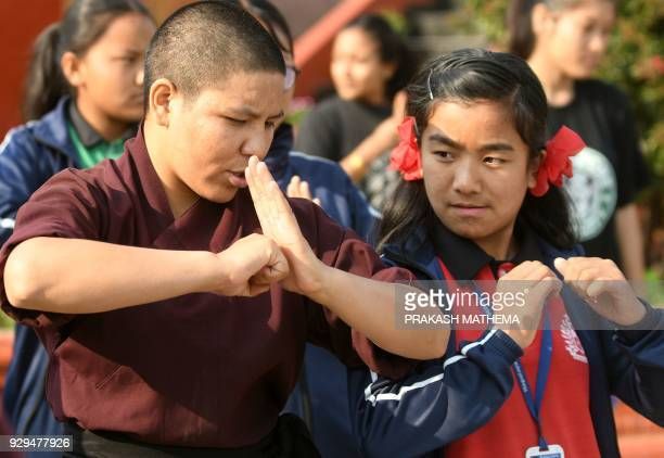 A Buddhist nun teaches kung fu to Nepali school students at the Amitabha Drukpa Nunnery during International Women's Day on the outskirts of...