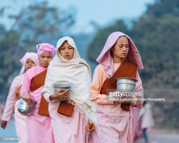 Buddhist nuns carrying ban bats, Hsipaw, Shan State, Myanmar