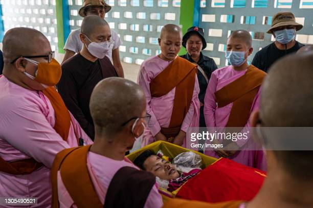 Buddhist nuns pay tribute to Zwal Htet Soe as his body lies in a coffin during a funeral for protesters who were shot dead in clashes with military...