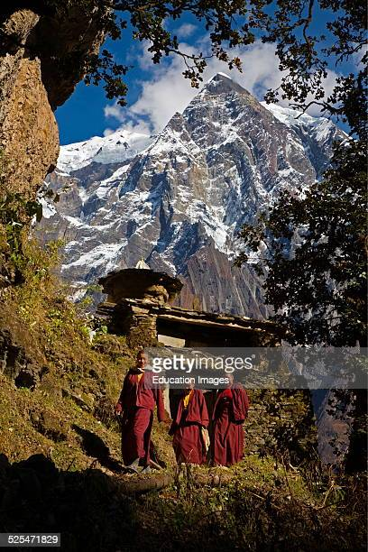 Buddhist Nuns Walks Through A Chorten Gateway In The Nupri Area Around Manaslu Trek Nepal