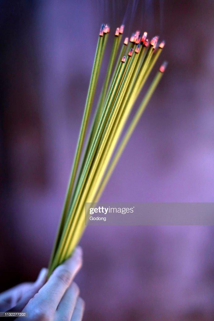 Buddhist pagoda  Woman praying with smoking Incense sticks