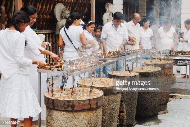 Buddhist people are lighting the oil lamps in gangaramya Temple - Colombo on the vesak festival day