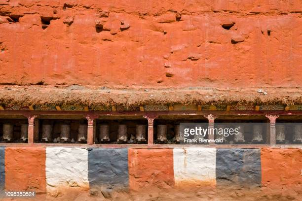Buddhist prayer wheels in a row at the orange painted wall of the Kag Chode Thupten Samphel Ling monastery