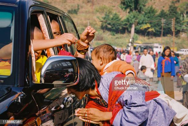 Buddhist spiritual leader of Bhutan Trulku Jigme Chode cutting hair from a baby from the car taking him along the route from the capital city Thimphu...