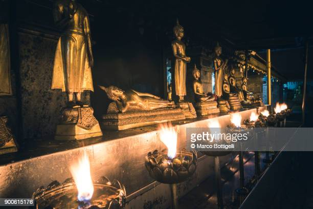 Buddhist statues with candles in a temple, Thailand.