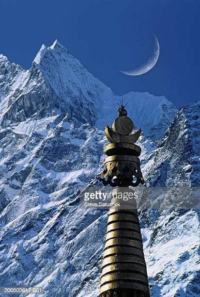 Buddhist stupa with mountain and moon, (digital composite)