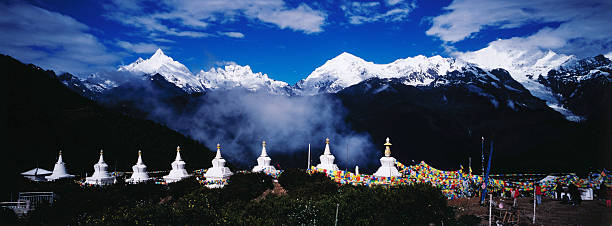 Buddhist stupas and prayer flags with Meili Xueshan mountain range in background.