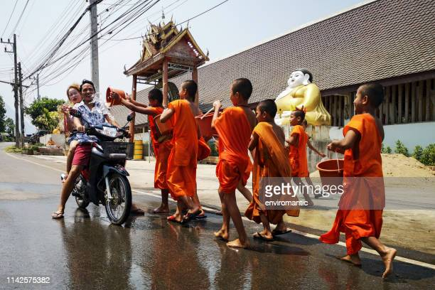 buddhist thai monks throwing water on people travelling on motorbikes on the road while passing the front of a thai buddhist temple during the songkran water festival and thai new year, chiang dao, northern thailand. - buddhist new year stock pictures, royalty-free photos & images