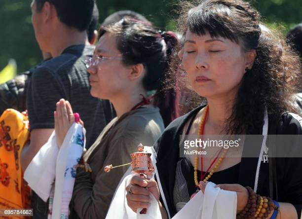 A Buddhist woman turns a small prayer wheel as she meditates waiting for the arrival of His Holiness the 17th Gyalwang Karmapa Ogyen Trinley Dorje...