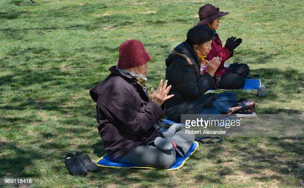 Buddhist women pray beside a Falun Dafa information display set up on the National Mall in Washington DC Falun Dafa also called Falun Gong is a...