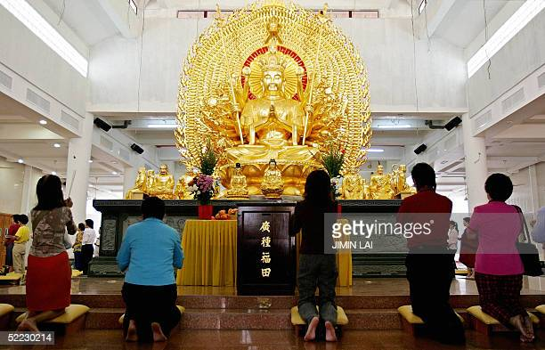Buddhists pray to a statue of Buddha at a Chinese temple in Kuala Lumpur 23 February 2005 on the fifteenth and last day of the Chinese New Year...