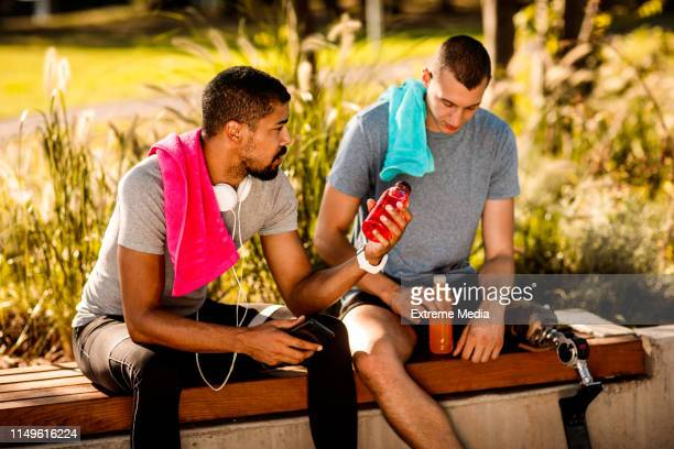buddies talking and resting after running session on a park bench - energy drink stock pictures, royalty-free photos & images