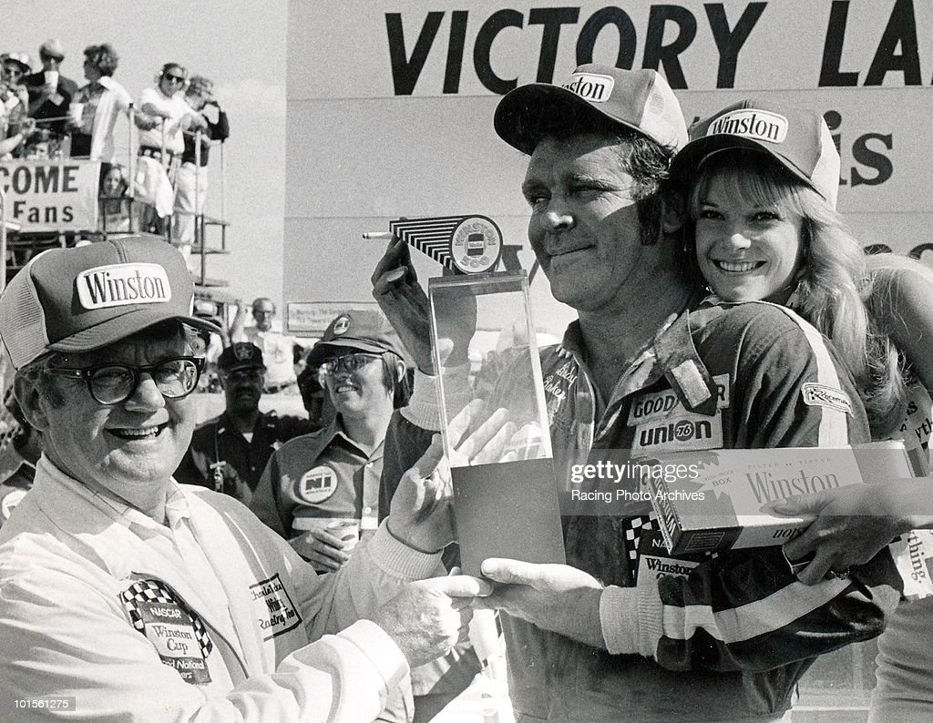 Buddy Baker accepts the trophy from Charles Tucker, Vice President and Director of Marketing, R.J. Reynolds Tobacco Co. as Bebop Hobel, Miss Winston looks on. Baker would take home $32,150 for the race.