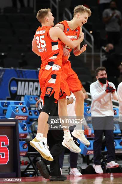 Buddy Boeheim and Marek Dolezaj of the Syracuse Orange celebrate their win over the West Virginia Mountaineers in their second round game of the 2021...