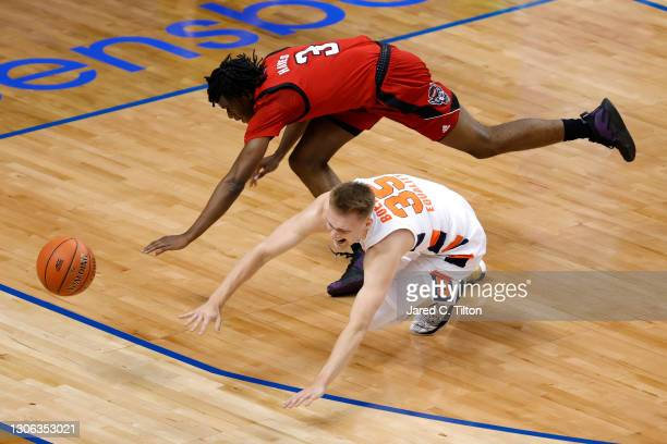 Buddy Boeheim of the Syracuse Orange and Cam Hayes of the North Carolina State Wolfpack battle for possession during the first half of their second...