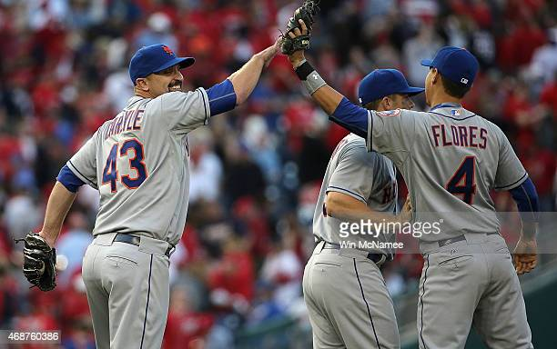Buddy Carlyle of the New York Mets celebrates with teammate Wilmer Flores after notching a save against the Washington Nationals on Opening Day at...