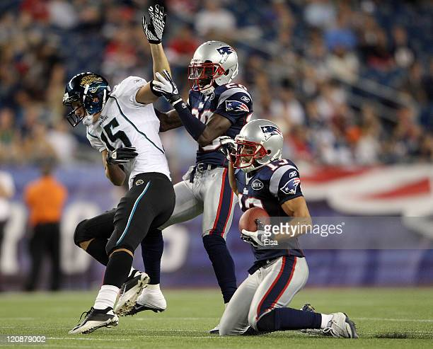 Buddy Farnham of the New England Patriots intercepts a pass intended for Greg Ellingson of the Jacksonville Jaguars as Darius Butler of the New...