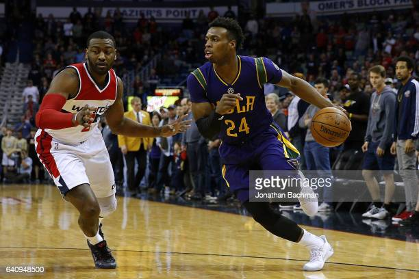 Buddy Hield of the New Orleans Pelicans drives against John Wall of the Washington Wizards during the first half of a game at the Smoothie King...