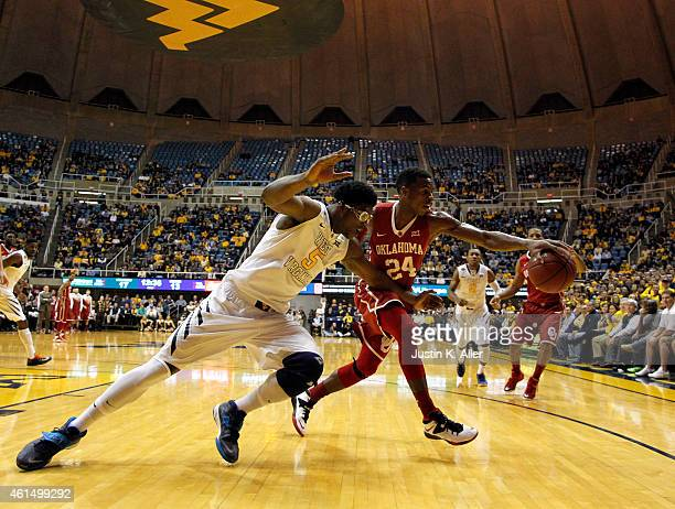Buddy Hield of the Oklahoma Sooners and Devin Williams of the West Virginia Mountaineers battle for a rebound during the game at the WVU Coliseum on...