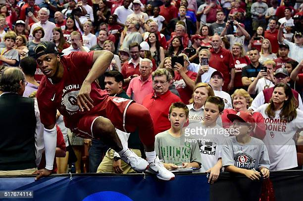 Buddy Hield of the Oklahoma Sooners climbs back onto the court after celebrating with fans after the Sooners 80-68 victory against the Oregon Ducks...