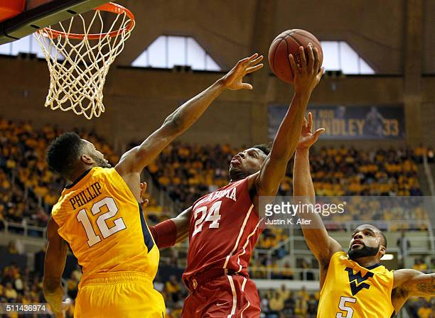 Buddy Hield of the Oklahoma Sooners drives to the basket during the game against Tarik Phillip and Jaysean Paige of the West Virginia Mountaineers at...