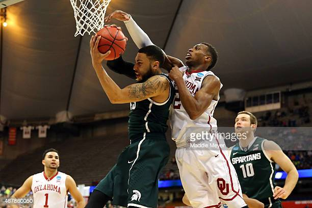 Buddy Hield of the Oklahoma Sooners fouls Denzel Valentine of the Michigan State Spartans late in the second half of the game during the East...