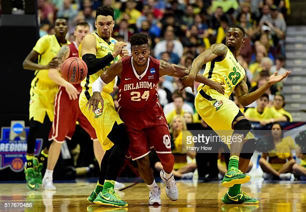 Buddy Hield of the Oklahoma Sooners goes for the ball between Dillon Brooks and Elgin Cook of the Oregon Ducks in the first half in the NCAA Men's...