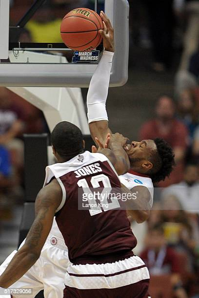 Buddy Hield of the Oklahoma Sooners goes to the basket and is fouled by Jalen Jones of the Texas AM Aggies during the West Regional Semifinal of the...