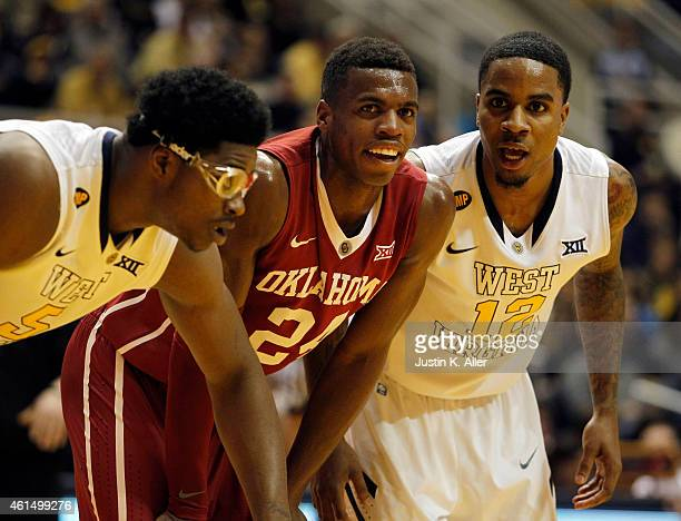 Buddy Hield of the Oklahoma Sooners looks on against Tarik Phillip and Devin Williams of the West Virginia Mountaineers during the game at the WVU...
