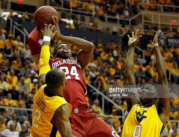 Buddy Hield of the Oklahoma Sooners pulls up for a shot against Jevon Carter and Teyvon Myers of the West Virginia Mountaineers during the game at...