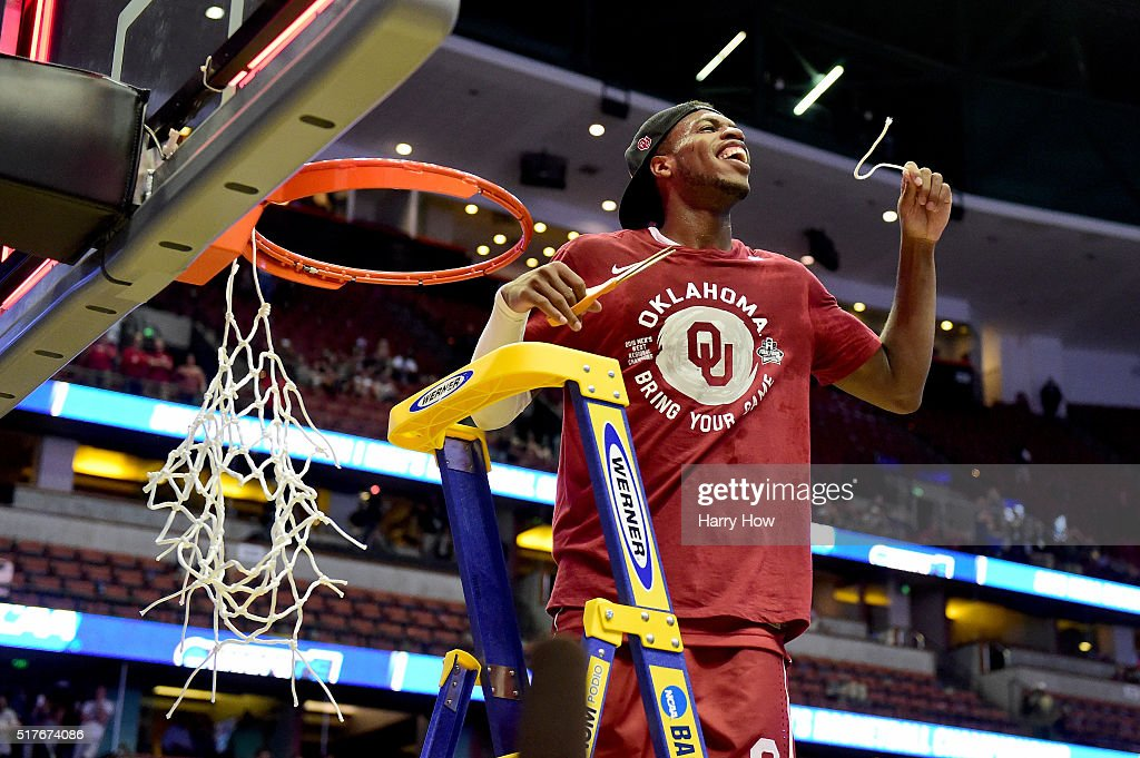 Buddy Hield #24 of the Oklahoma Sooners smiles after cutting a piece of the net after the Sooners 80-68 victory against the Oregon Ducks in the NCAA Men's Basketball Tournament West Regional Final at Honda Center on March 26, 2016 in Anaheim, California.