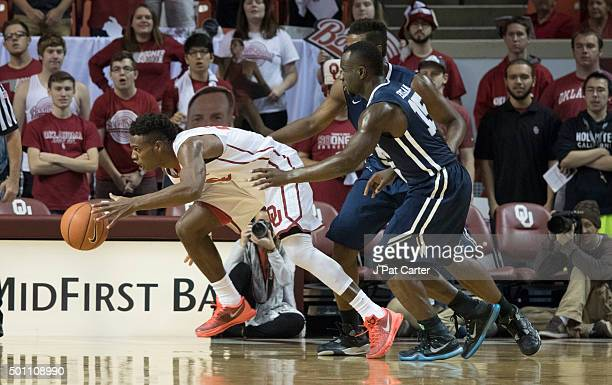 Buddy Hield of the Oklahoma Sooners steals the ball away from Obi Emegano and Brandon Conley of the Oral Roberts Golden Eagles during the first half...