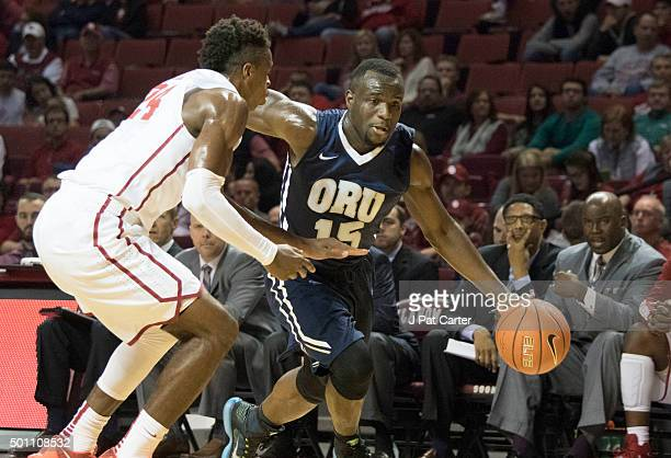 Buddy Hield of the Oklahoma Sooners tries to block Obi Emegano of the Oral Roberts Golden Eagles during the first half of NCAA college basketball...