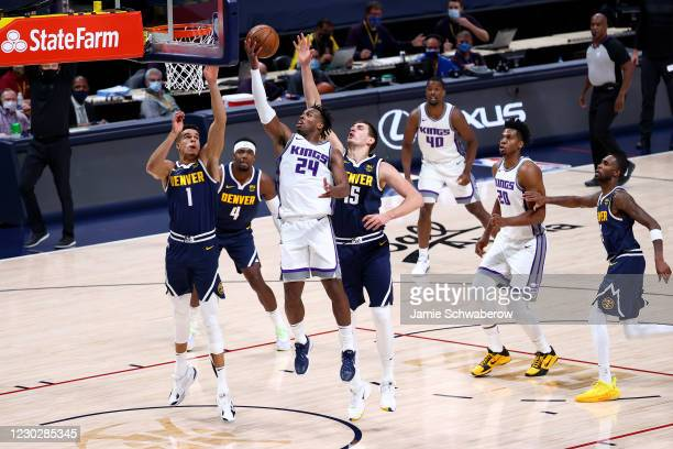Buddy Hield of the Sacramento Kings drives to the basket against Nikola Jokic of the Denver Nuggets at Ball Arena on December 23, 2020 in Denver,...