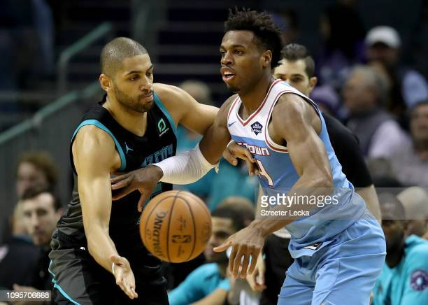 Buddy Hield of the Sacramento Kings passes the ball around Nicolas Batum of the Charlotte Hornets during their game at Spectrum Center on January 17...