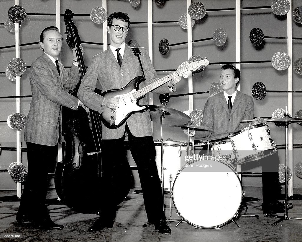 Buddy Holly And The The Crickets, (L-R) Joe B Mauldin, Buddy Holly (with Fender Stratocaster guitar) and Jerry Allison, pose for a group shot on the set of the BBC television show 'Off The Record' during their UK tour.