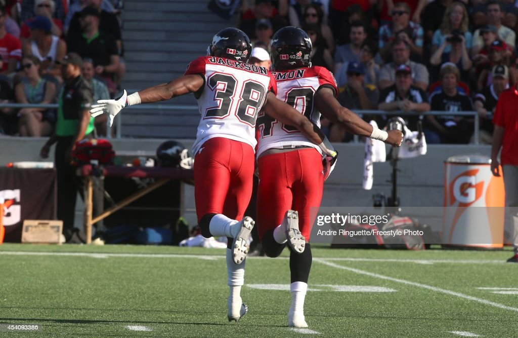 Buddy Jackson #38 and Shawn Lemon #40 of the Calgary Stampeders celebrate a quarterback sack against the Ottawa Redblacks during a CFL game at TD Place Stadium on August 24, 2014 in Ottawa, Ontario, Canada.