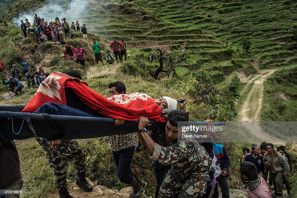 Buddy Prasad Grg, 45 is carried by villagers and Nepalese soldiers towards an Indian helicopter after being injured during an aftershock on May 6, 2015 in Lampuk, Nepal. A major 7.9 earthquake hit Kathmandu mid-day on Saturday 25th April, and was followed by multiple aftershocks that triggered avalanches on Mt. Everest that buried mountain climbers in their base camps. Many houses, buildings and temples in the capital were destroyed during the earthquake, leaving over 7000 dead and many more trapped under the debris as emergency rescue workers attempt to clear debris and find survivors. Regular aftershocks have hampered recovery missions as locals, officials and aid workers attempt to recover bodies from the rubble.