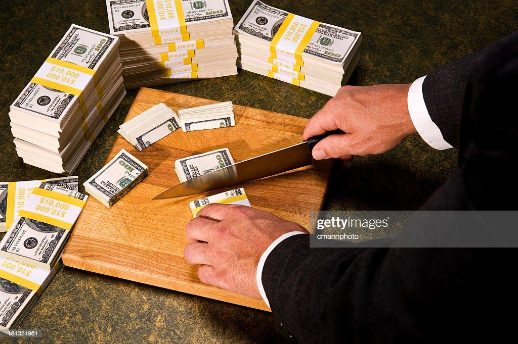 Budget Cutting - Congressman cutting stacks of money : Stock Photo