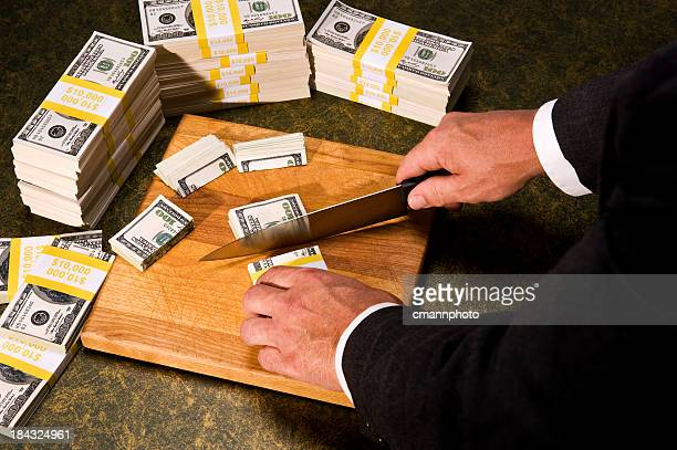 budget cutting - congressman cutting stacks of money - fat cat stock photos and pictures