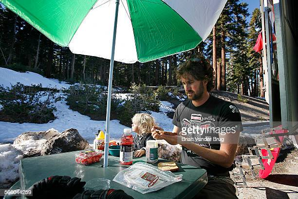 Budget–minded snowboarder Ryan Groat and son Luka of Huntington Beach make turkey sandwiches while parked in the lot near chair 2 at Mammoth Mountain...