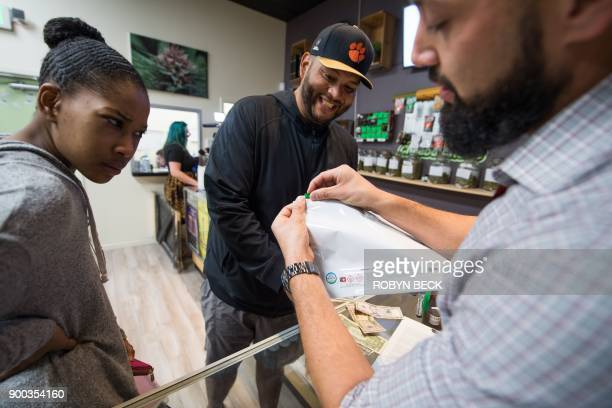 Budtender Danny Buelna shows customers Mariah Roy and Edward Ochoa how to use the required childproof bag for their purchases at the Green Pearl...