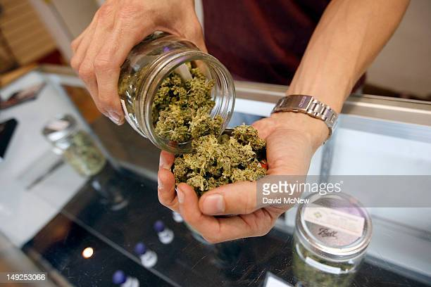 A budtender pours marijuana from a jar at Perennial Holistic Wellness Center medical marijuana dispensary which opened in 2006 on July 25 2012 in Los...