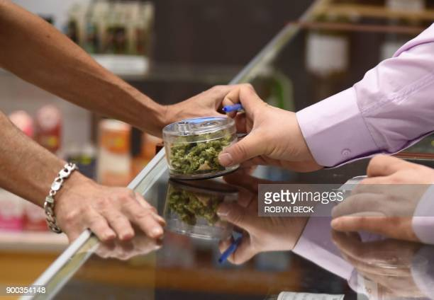 A budtender shows cannabis buds to a customer at the Green Pearl Organics dispensary on the first day of legal recreational marijuana sales in...