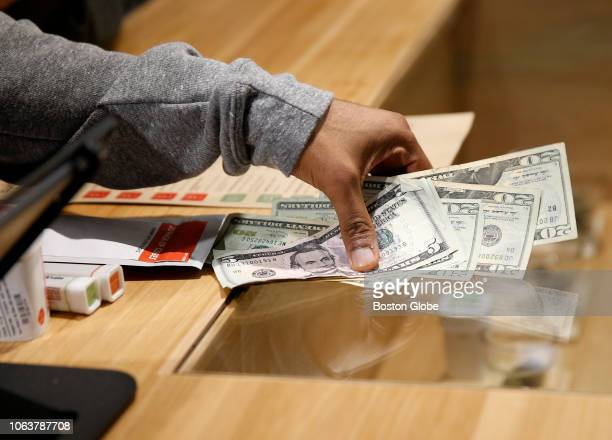 A budtender takes Brittani Beeso's money as she purchases marijuana at the opening of Cultivate one of the state's first two pot shops in Leicester...